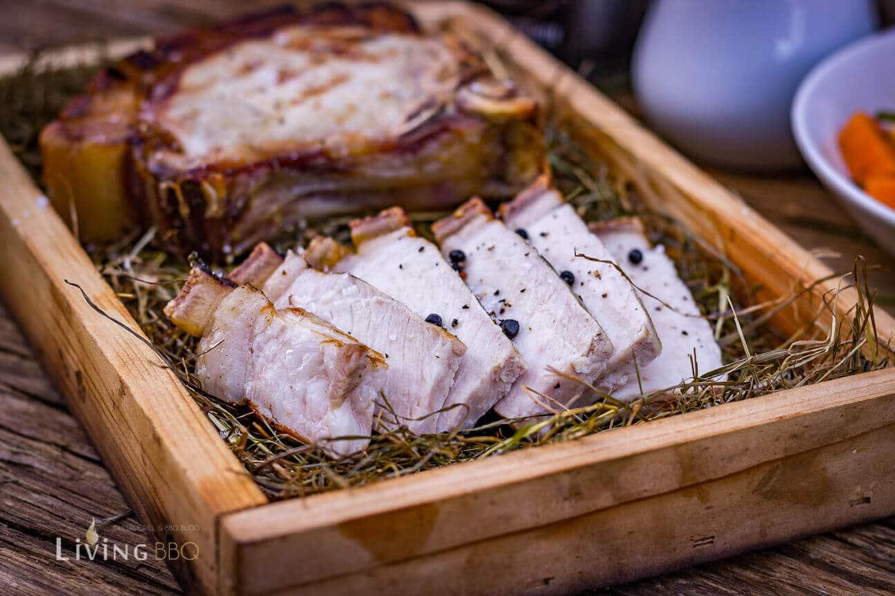 Dry Aged Schweinekotelett in der Holzbox serviert.