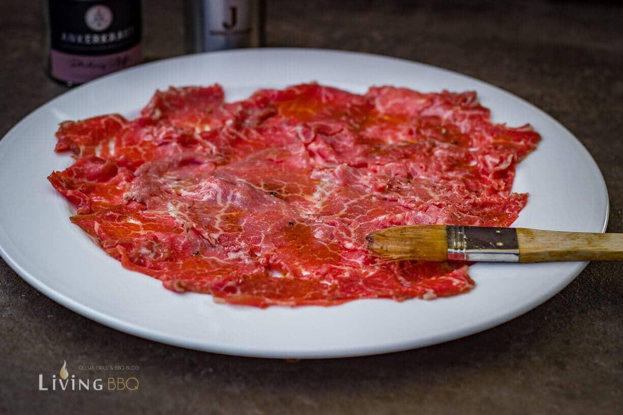 Rinderfilet auf dem Teller anrichten und mit vinaigrette bestreichen
