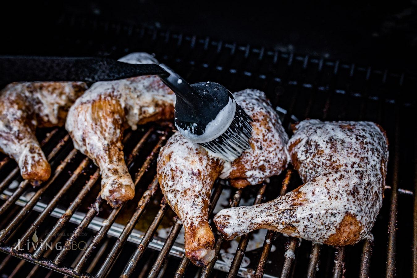 Weiße Barbecue Sauce auf das Fleisch pinseln