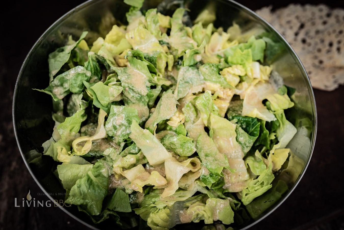 Romana Salat mit dem Dressing vermischen